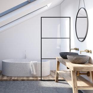 Modelo de cuarto de baño con ducha, nórdico, con armarios abiertos, bañera exenta, paredes blancas, suelo de cemento, lavabo sobreencimera, encimera de madera, suelo gris y encimeras beige