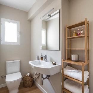 Foto de cuarto de baño mediterráneo con paredes beige, suelo de madera en tonos medios y lavabo suspendido