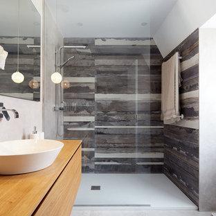 Diseño de cuarto de baño actual con armarios con paneles lisos, puertas de armario de madera oscura, ducha empotrada, baldosas y/o azulejos grises, paredes blancas, lavabo sobreencimera, encimera de madera, ducha abierta y encimeras marrones