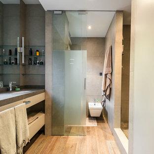 Exempel på ett mellanstort modernt en-suite badrum, med öppna hyllor, en dusch i en alkov, en bidé, beige väggar, skåp i ljust trä, grå kakel, cementkakel, ljust trägolv, ett undermonterad handfat och bänkskiva i betong
