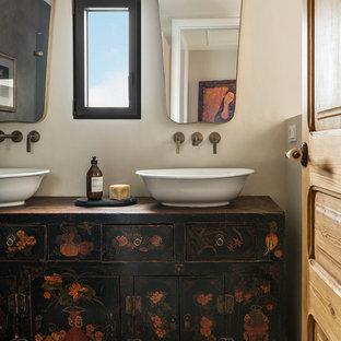 Diseño de cuarto de baño mediterráneo, de tamaño medio, con armarios tipo mueble, puertas de armario con efecto envejecido, baldosas y/o azulejos multicolor, baldosas y/o azulejos de cerámica, paredes beige, suelo de baldosas de cerámica, lavabo sobreencimera, encimera de madera, suelo multicolor y encimeras negras