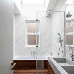 Ejemplo de cuarto de baño con ducha, moderno, pequeño, con armarios tipo mueble, puertas de armario de madera oscura, bañera encastrada, combinación de ducha y bañera, sanitario de pared, baldosas y/o azulejos blancos, baldosas y/o azulejos de mármol, paredes blancas, suelo de cemento, lavabo suspendido, encimera de mármol, suelo gris, ducha con puerta con bisagras y encimeras grises