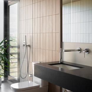 Imagen de cuarto de baño con ducha, contemporáneo, grande, con armarios abiertos, puertas de armario negras, ducha empotrada, sanitario de una pieza, baldosas y/o azulejos beige, paredes beige, lavabo bajoencimera y encimeras negras