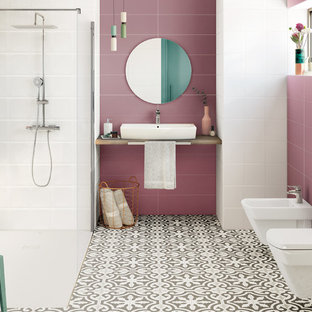 Photo of a contemporary bathroom in Barcelona with beige cabinets, a built-in shower, a wall mounted toilet, pink tiles, pink walls, a vessel sink, an open shower and beige worktops.