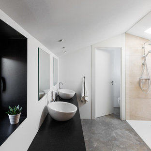 Photo of a large contemporary master bathroom in Madrid with flat-panel cabinets, a curbless shower, beige tile, ceramic tile, white walls, concrete floors, a vessel sink, granite benchtops, grey floor, black benchtops and an open shower.