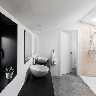 Imagen de cuarto de baño principal, contemporáneo, grande, con armarios con paneles lisos, ducha a ras de suelo, baldosas y/o azulejos beige, baldosas y/o azulejos de cerámica, paredes blancas, suelo de cemento, lavabo sobreencimera, encimera de granito, suelo gris, encimeras negras y ducha abierta