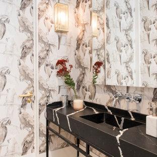 Diseño de cuarto de baño actual con paredes multicolor, suelo de madera clara, lavabo integrado, suelo beige y encimeras negras