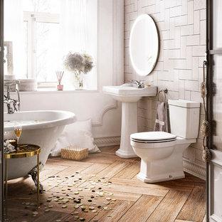 Foto de cuarto de baño de estilo de casa de campo con puertas de armario blancas, bañera con patas, sanitario de dos piezas, baldosas y/o azulejos beige, paredes blancas, suelo de madera en tonos medios, lavabo con pedestal, suelo beige y encimeras blancas
