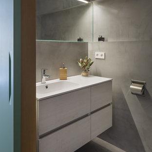 Foto de cuarto de baño principal, contemporáneo, pequeño, con armarios con paneles lisos, puertas de armario blancas, ducha a ras de suelo, sanitario de pared, baldosas y/o azulejos grises, paredes grises, suelo de cemento, lavabo de seno grande, encimera de cuarzo compacto, suelo gris y ducha abierta