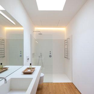 Diseño de cuarto de baño con ducha, contemporáneo, de tamaño medio, con ducha a ras de suelo, sanitario de pared, paredes blancas, suelo de madera en tonos medios, lavabo integrado y ducha abierta