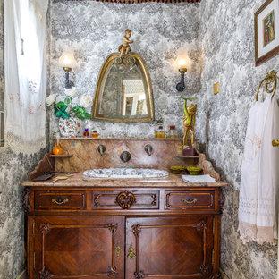 Modelo de cuarto de baño bohemio con armarios tipo mueble, puertas de armario de madera en tonos medios, paredes grises, lavabo encastrado, suelo beige y encimeras marrones