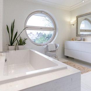 Ejemplo de cuarto de baño con ducha, actual, de tamaño medio, con armarios con paneles lisos, puertas de armario blancas, bañera encastrada, paredes grises, lavabo bajoencimera, suelo blanco y encimeras blancas