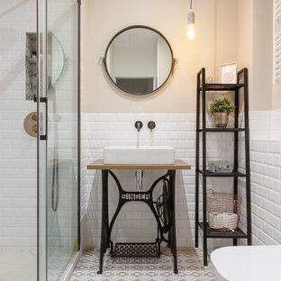 Foto de cuarto de baño con ducha, escandinavo, con armarios abiertos, ducha empotrada, baldosas y/o azulejos blancos, baldosas y/o azulejos de cemento, paredes beige, lavabo sobreencimera, encimera de madera, suelo beige, ducha con puerta corredera y encimeras marrones