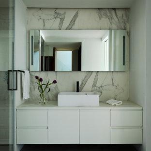 Ejemplo de cuarto de baño actual con armarios con paneles lisos, puertas de armario blancas, baldosas y/o azulejos blancos, losas de piedra, paredes blancas, lavabo sobreencimera, suelo gris y encimeras blancas