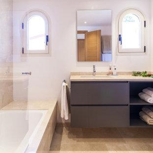 Modelo de cuarto de baño con ducha, contemporáneo, de tamaño medio, con armarios con paneles lisos, puertas de armario grises, bañera encastrada, sanitario de pared, baldosas y/o azulejos beige, baldosas y/o azulejos de porcelana, paredes blancas, suelo de baldosas de porcelana, lavabo bajoencimera, suelo beige y encimeras beige
