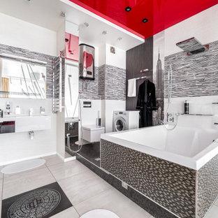 Modernes Badezimmer mit Eckbadewanne, Duschbadewanne, Wandtoilette, schwarz-weißen Fliesen, grauem Boden, Duschvorhang-Duschabtrennung, weißer Waschtischplatte, Wäscheaufbewahrung, Einzelwaschbecken und schwebendem Waschtisch