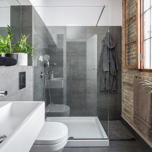 Imagen de cuarto de baño con ducha, industrial, de tamaño medio, con lavabo de seno grande, ducha esquinera, paredes grises, baldosas y/o azulejos grises, losas de piedra y suelo de baldosas de cerámica