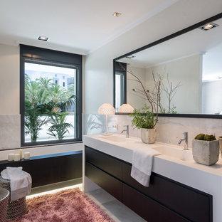Ejemplo de cuarto de baño contemporáneo con armarios con paneles lisos, puertas de armario negras, bañera encastrada sin remate, baldosas y/o azulejos grises, paredes blancas, lavabo integrado, suelo gris y encimeras blancas