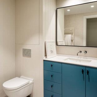 Foto de cuarto de baño nórdico con armarios tipo mueble, puertas de armario azules, sanitario de pared, suelo gris, encimeras blancas, paredes beige y lavabo bajoencimera