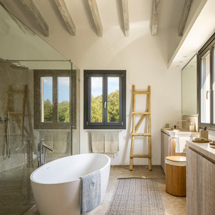 Design ideas for a mediterranean ensuite bathroom in Other with flat-panel cabinets, light wood cabinets, a freestanding bath, a built-in shower, grey tiles, white walls, brown floors, a hinged door and beige worktops.