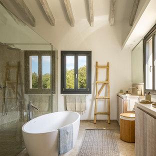 Diseño de cuarto de baño principal, mediterráneo, con armarios con paneles lisos, puertas de armario de madera clara, bañera exenta, ducha a ras de suelo, baldosas y/o azulejos grises, paredes blancas, suelo marrón, ducha con puerta con bisagras y encimeras beige