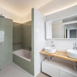 Foto de cuarto de baño principal, actual, con armarios abiertos, puertas de armario de madera clara, bañera empotrada, baldosas y/o azulejos verdes, baldosas y/o azulejos blancos, lavabo sobreencimera, encimera de madera, ducha abierta, ducha abierta, suelo gris y encimeras beige