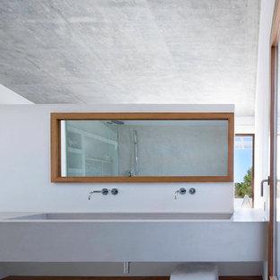 Modelo de cuarto de baño principal, contemporáneo, grande, con lavabo de seno grande, armarios abiertos, puertas de armario de madera oscura, paredes grises, suelo de cemento y encimera de cemento