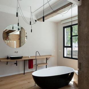 Foto de cuarto de baño principal, contemporáneo, grande, con suelo de madera en tonos medios, bañera exenta, paredes grises, lavabo sobreencimera, encimera de madera, suelo beige y encimeras beige