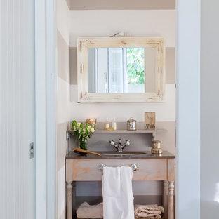 Modelo de cuarto de baño romántico con armarios abiertos, puertas de armario con efecto envejecido y paredes beige