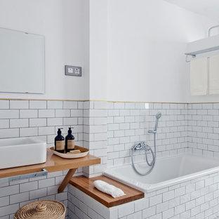 Modelo de cuarto de baño escandinavo con bañera encastrada, baldosas y/o azulejos blancos, baldosas y/o azulejos de cemento, paredes blancas, lavabo sobreencimera, suelo multicolor y ducha con puerta con bisagras