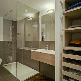 Diseño de cuarto de baño contemporáneo con armarios con paneles lisos, puertas de armario de madera clara, ducha esquinera, baldosas y/o azulejos grises, suelo de madera oscura, lavabo encastrado y ducha abierta