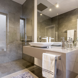 Ejemplo de cuarto de baño moderno con ducha a ras de suelo, baldosas y/o azulejos grises, paredes blancas, lavabo sobreencimera, suelo gris y encimeras grises