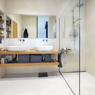 Imagen de cuarto de baño con ducha, contemporáneo, con armarios abiertos, puertas de armario de madera oscura, ducha a ras de suelo, lavabo sobreencimera, encimera de madera, paredes beige, suelo de cemento, suelo beige, ducha abierta y encimeras marrones