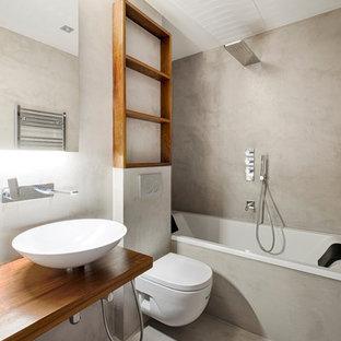 Modelo de cuarto de baño principal, contemporáneo, de tamaño medio, con bañera empotrada, combinación de ducha y bañera, sanitario de pared, paredes grises, suelo de cemento, lavabo sobreencimera, encimera de madera, suelo gris, encimeras marrones y ducha abierta