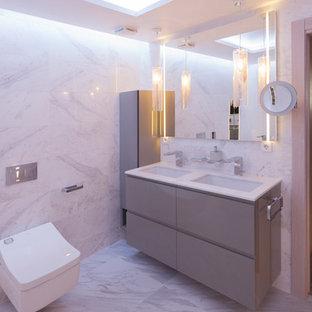 Immagine di una stanza da bagno contemporanea con ante grigie, WC sospeso, piastrelle bianche, piastrelle beige, piastrelle grigie, ante lisce, pareti grigie, pavimento grigio, top bianco e lavabo sottopiano