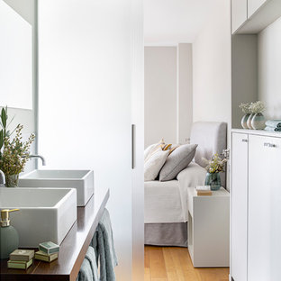 Modelo de cuarto de baño principal, actual, con armarios con paneles lisos, puertas de armario blancas, paredes grises, lavabo sobreencimera, encimera de madera, suelo gris y encimeras marrones