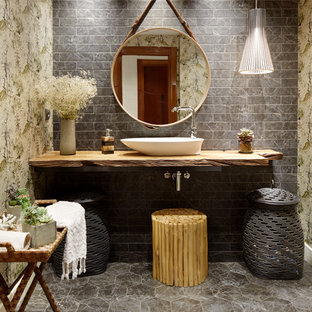 Design ideas for a world-inspired bathroom in Other with grey tiles, metro tiles, a vessel sink, wooden worktops, grey floors and brown worktops.