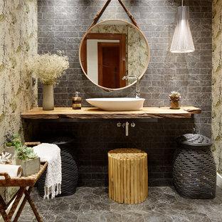 Asiatisches Badezimmer mit grauen Fliesen, Metrofliesen, Aufsatzwaschbecken, Waschtisch aus Holz, grauem Boden und brauner Waschtischplatte in Sonstige