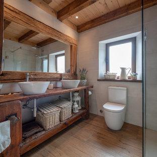 バルセロナのカントリー風おしゃれな浴室 (オープンシェルフ、濃色木目調キャビネット、白いタイル、白い壁、無垢フローリング、ベッセル式洗面器、木製洗面台、茶色い床、ブラウンの洗面カウンター、洗面台2つ、独立型洗面台、表し梁、三角天井、板張り天井) の写真