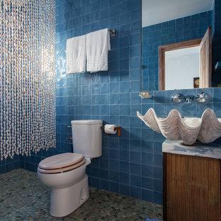 Foto de cuarto de baño con ducha, tropical, de tamaño medio, con lavabo sobreencimera, sanitario de dos piezas, baldosas y/o azulejos azules, ducha abierta, baldosas y/o azulejos de cerámica, paredes azules, suelo de baldosas tipo guijarro, encimera de mármol, armarios tipo mueble, puertas de armario de madera oscura y ducha con cortina