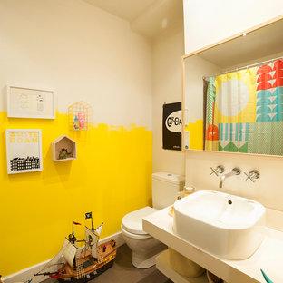 Esempio di una piccola stanza da bagno per bambini bohémian con lavabo a bacinella, WC a due pezzi, pareti gialle, pavimento in cemento e top in superficie solida
