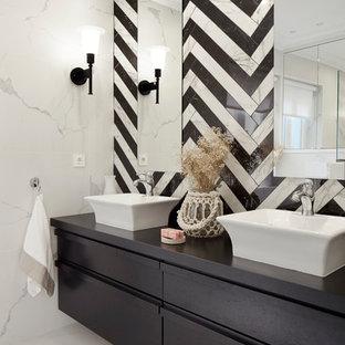 Ejemplo de cuarto de baño contemporáneo con armarios con paneles lisos, puertas de armario negras, baldosas y/o azulejos blancas y negros, paredes blancas, lavabo sobreencimera, encimera de madera y suelo blanco