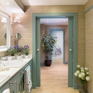 Modelo de cuarto de baño principal, costero, con puertas de armario verdes, paredes beige y lavabo encastrado