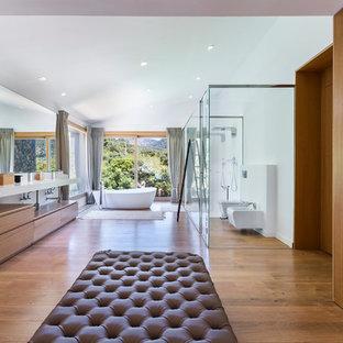 Idées déco pour une très grand salle de bain principale contemporaine avec des portes de placard en bois brun, une baignoire indépendante, une douche à l'italienne, un WC suspendu, un placard à porte plane, un sol en bois brun, un lavabo intégré et un mur blanc.