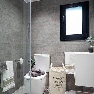 Modelo de cuarto de baño con ducha, escandinavo, pequeño, con armarios con paneles lisos, puertas de armario blancas, ducha a ras de suelo, sanitario de dos piezas y lavabo suspendido