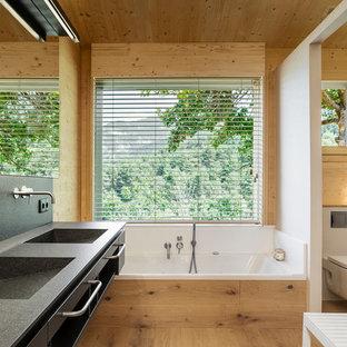 Imagen de cuarto de baño principal, moderno, con armarios con paneles lisos, puertas de armario negras, bañera empotrada, sanitario de pared, paredes blancas, suelo de madera clara, lavabo integrado y encimeras negras