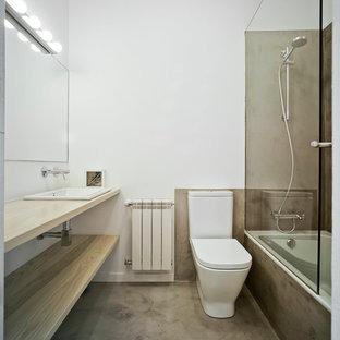 Diseño de cuarto de baño principal, actual, de tamaño medio, con armarios abiertos, puertas de armario de madera clara, bañera encastrada, combinación de ducha y bañera, sanitario de una pieza, paredes blancas, lavabo encastrado, encimera de madera, suelo de cemento y suelo gris