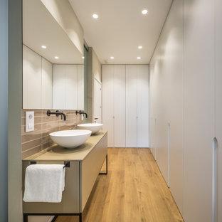 Modelo de cuarto de baño con ducha, actual, de tamaño medio, con armarios tipo mueble, puertas de armario beige, baldosas y/o azulejos grises, baldosas y/o azulejos en mosaico, paredes grises, suelo de madera en tonos medios, lavabo sobreencimera, suelo beige y encimeras beige