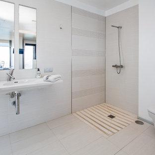 Imagen de cuarto de baño actual con ducha esquinera, baldosas y/o azulejos grises, paredes blancas, lavabo integrado, suelo gris, ducha abierta y encimeras blancas