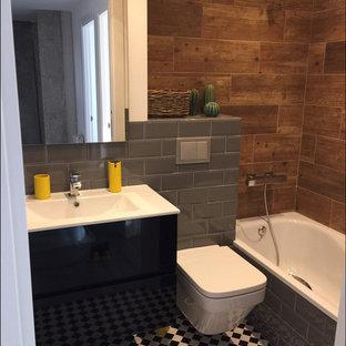 Foto de cuarto de baño infantil, urbano, pequeño, con armarios tipo mueble, puertas de armario negras, bañera encastrada, sanitario de pared, baldosas y/o azulejos grises, baldosas y/o azulejos en mosaico, paredes marrones, suelo de baldosas de cerámica, lavabo integrado y suelo blanco
